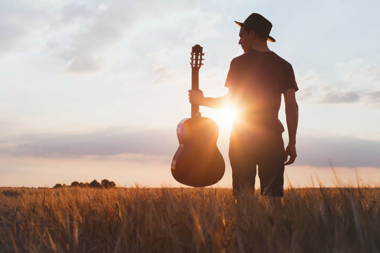 Silhouette of guitarist in field at sunset.