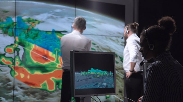 Climate scientists studying images of hurricanes as a consequence of climate change.