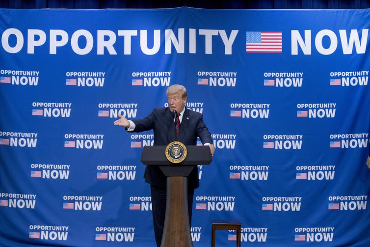 Trump at a podium pointing with an Opportunity Now banner behind him