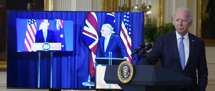 Joe Biden stands at a podium with Boris Johnson and Scott Morrison on screens beside him.