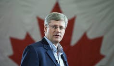 Harper speaks with a Canadian flag behind him.