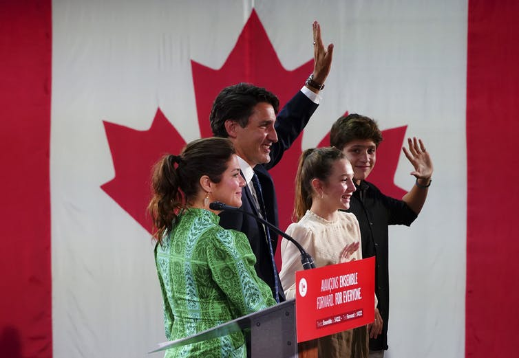 Trudeau and his family wave to supporters with a Canadian flag beside them.