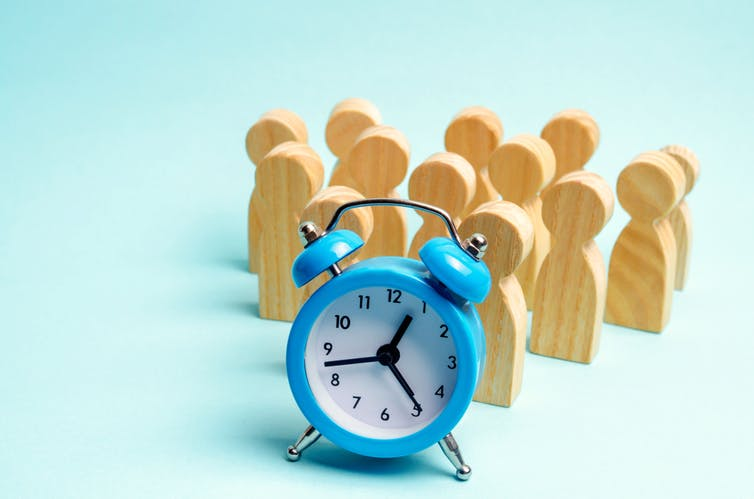 Wooden figures of people behind an alarm clock