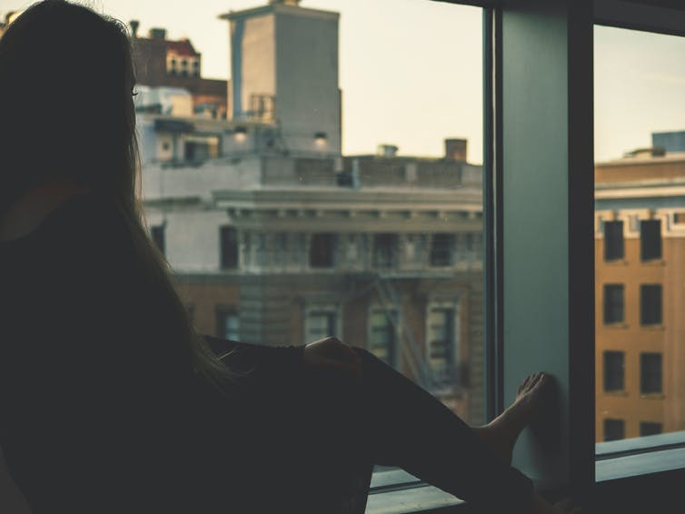 A woman looks out a window at a city street.