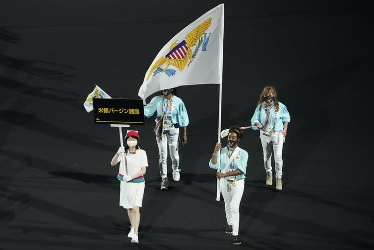 Four people march carrying a flag.