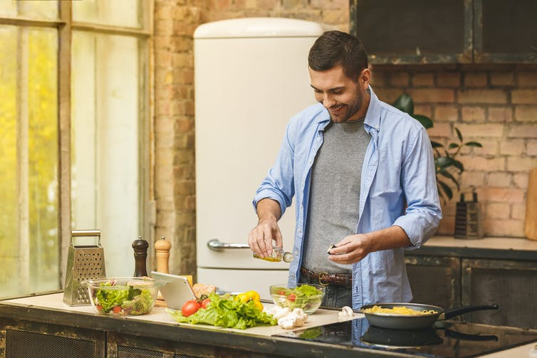 Young man in a blue shirt puts salt into a salad bowl while cooking in a kitchen.