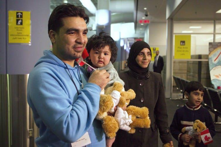 A man holds a baby and two teddy bears and smiles as his smiling wife and son, holding a small Canadian flag, stand beside him.