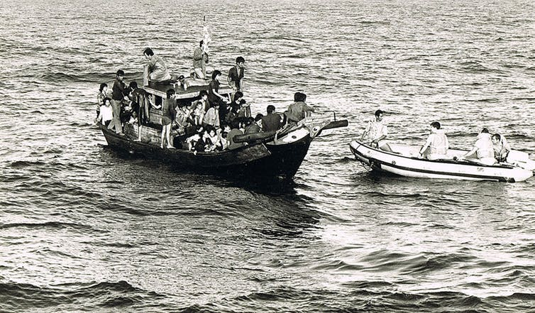 People are seen crammed onto a small boat in a black and white photo.