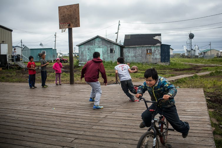 Children play basketball and ride bikes on a large wooden platform above the wet ground. Weather-beaten houses stand in the background.