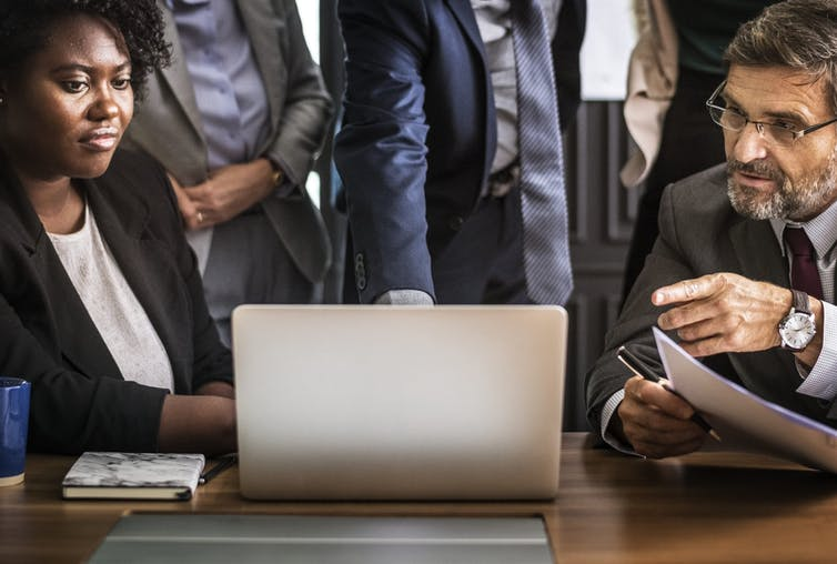 People looking stern-faced gather around a laptop in an office setting.
