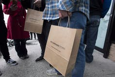 Brown paper shopping bags from the B.C. Cannabis Store carried by customers