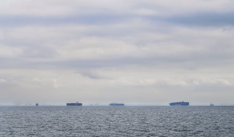 Cargo ships filled with containers idle in waters off of California on a cloudy day as they await entry to the Port of Los Angeles or Port of Long Beach