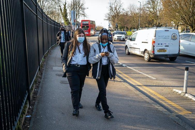 Two girls in masks leaving school