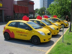 Delivery automobiles with the St-Hubert logo in a parking lot.