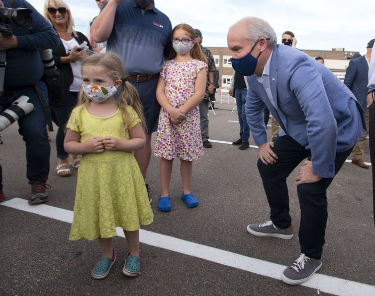 Erin O'Toole leans on his knees to speak to a young girl.