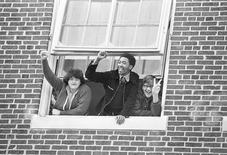 Several students wave and cheer through a window in a brick building