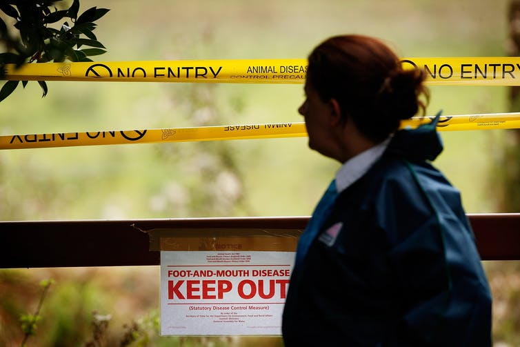 A woman stands in front of an area cordoned off with caution tape and a sign saying 'Keep Out.'