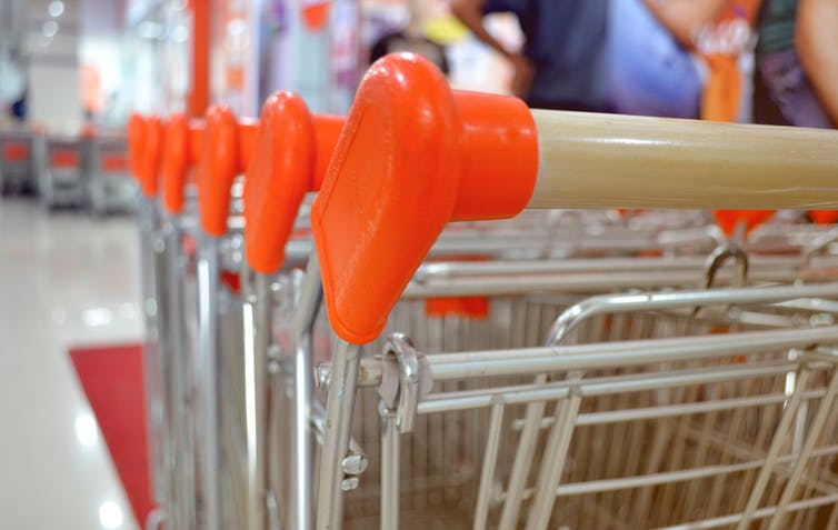 close up of shopping cart handles in foreground with grocery aisle out-of-focus in background