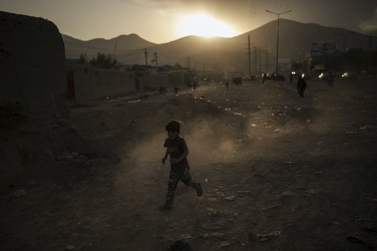 An Afghan boy plays beside a road as the sun sets.