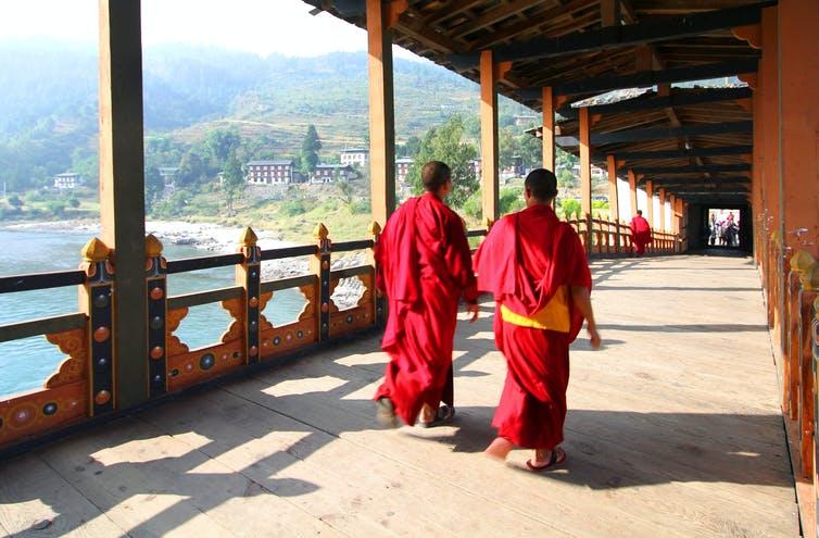 Two Buddhist monks walking over a bridge