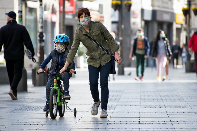 A mother walking on a paved street, helps her child who is riding a bike.